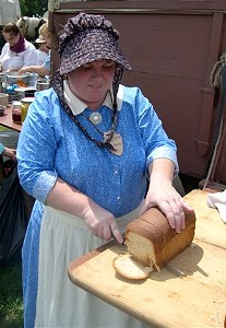 A gal slicing bread in pioneer clothing during the Ft. Seward wagon train, photo by S. Kluvers