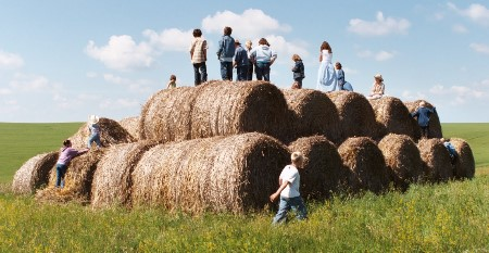Children untop of hay bale stack, photo by J. Turner